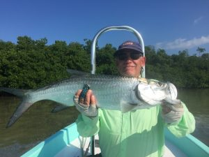 Angler with a small tarpon caught from Belize River Lodge.