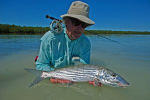 Angler in water with bonefish. Brand Bahama, H2O Bonfishing.