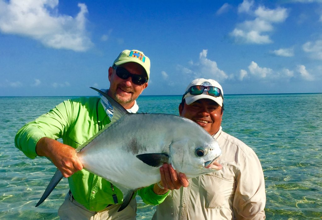 Angler and guide with a permit caught while fishing Ascension Bay Mexico at Casa Blanca lodge.