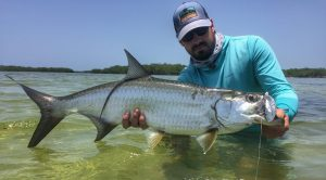 Angler in the water with a small tarpon caught while fishing with La Pescadora Lodge in Punta Allen Mexico.