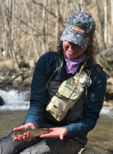 Female angler with a brook trout caught on a fly fishing guide trip.