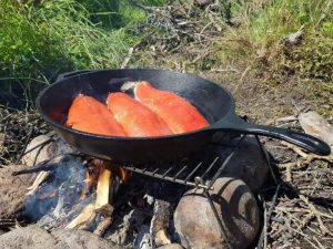Salmon being cooked for a shore lunch while fishing with Alaska Trophy Adventures.
