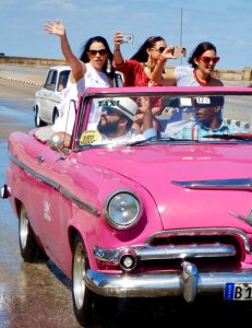Old car with girls waving while driving along the malecon. Down town Havanna.