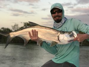 Angler with a small tarpon at sunset in Cuba.