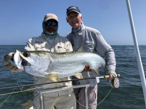 Fly fishing guide and angler with a tarpon caught in Isla de la Juventud, Cuba. Fly fishing from Avalon 1 fleet mother ship.