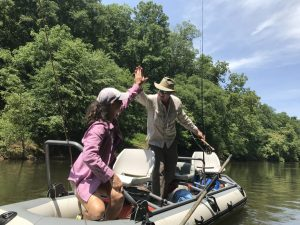 Female angler and fishing guide in boat flaoting a Virginia smallmouth river.
