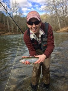 A happy female angler holding a nice rainbow caught during the ladies fly fishing lesson with a Virginia fishing guide.
