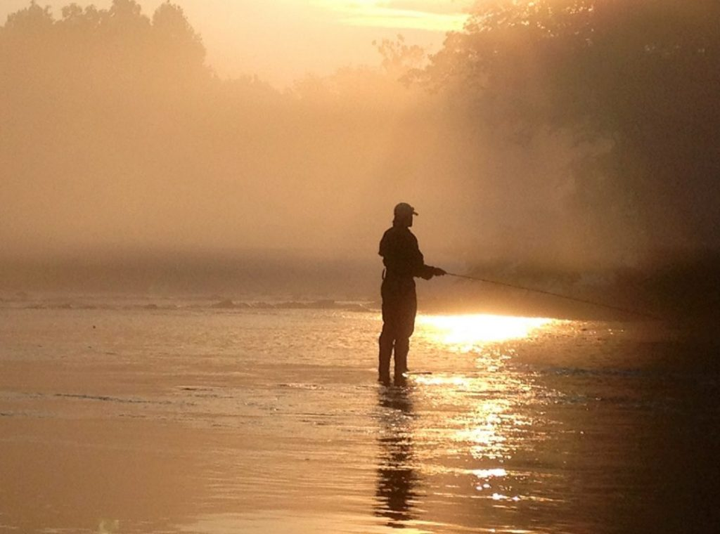 An angler from Sachem's pass stands in the river while the sun rises.