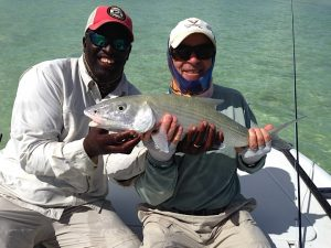 Very happy angler and guide with bonefish while fishing Swains Cay Lodge, Andros Island Bahamas.