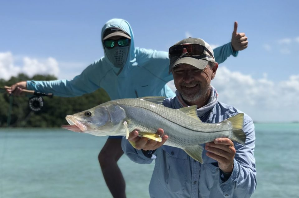 Two anglers holding a snook caught in Ascension Bay Mexico on the Yucatan Peninsula, Mexico.
